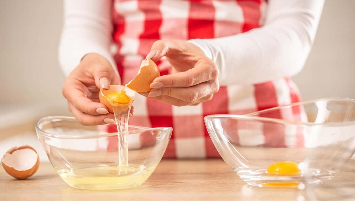 Woman separating egg yolks from the whites into two glass bowls