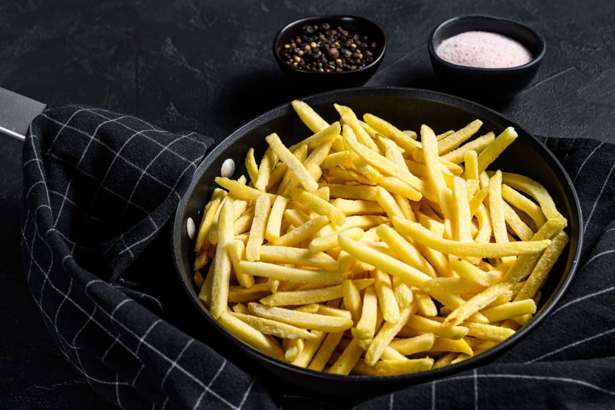 Frozen French fries in a frying pan, How To Blanch French Fries [And Should You?]