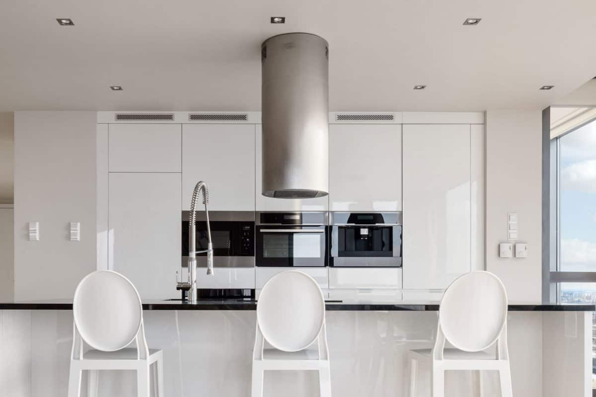 Gorgeous white designed kitchen with a black countertop on the kitchen and breakfast bar