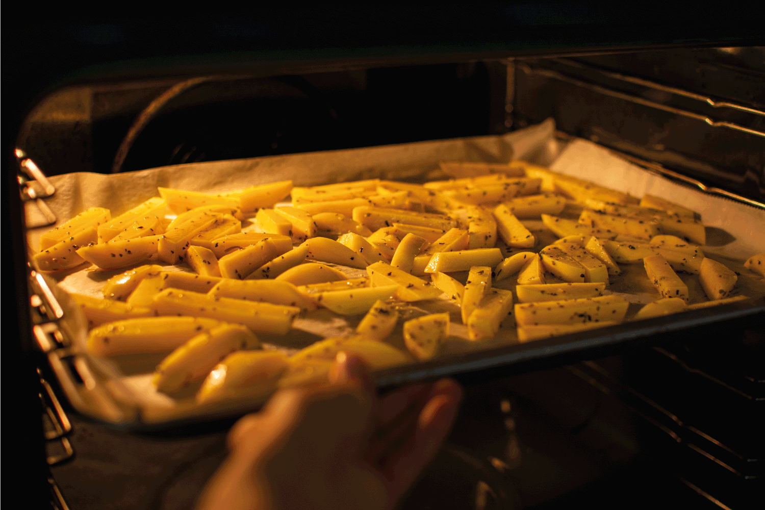 Hand putting tray with cut potatoes into the oven to make a healthy homemade french fries