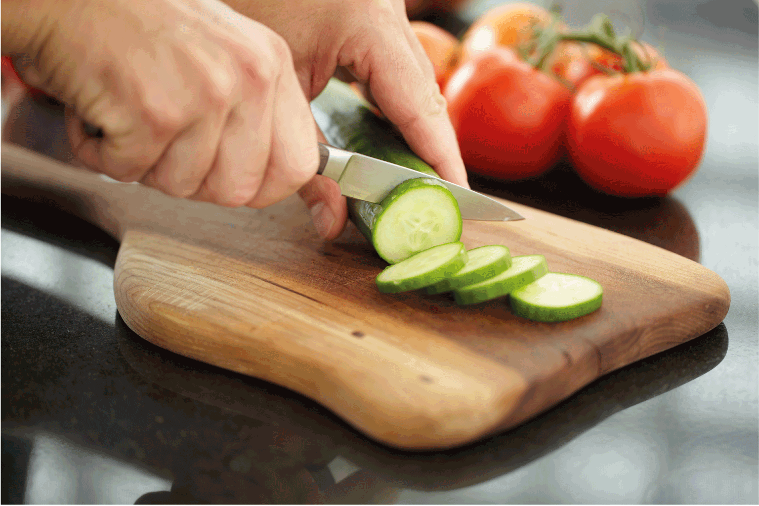 Hands slicing cucumber on rustic cutting board with paring knife with tomatoes in background