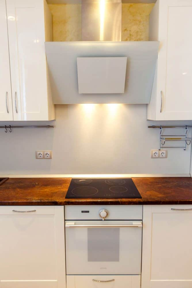 Hardwood kitchen countertop and white kitchen cabinets with an electric induction cooker