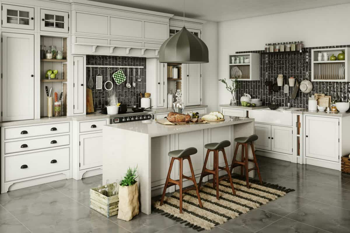 Interior of a kitchen inspired with a white and cozy design, a small breakfast bar with small wooden bar stools, and a huge dangling lamp on the center