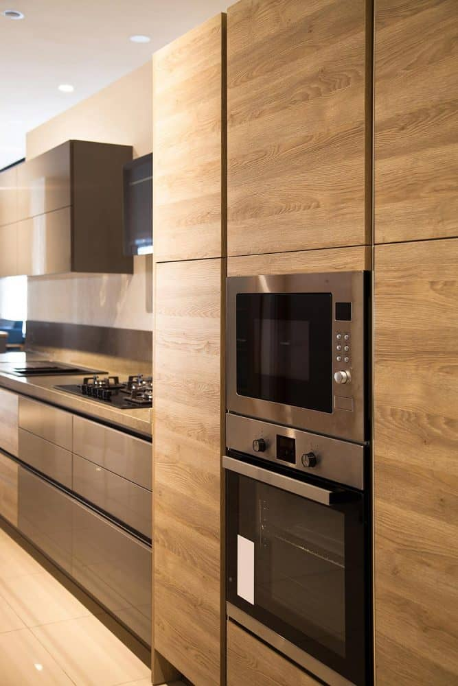 Interior of modern kitchen equipment with grey and oak cabinets