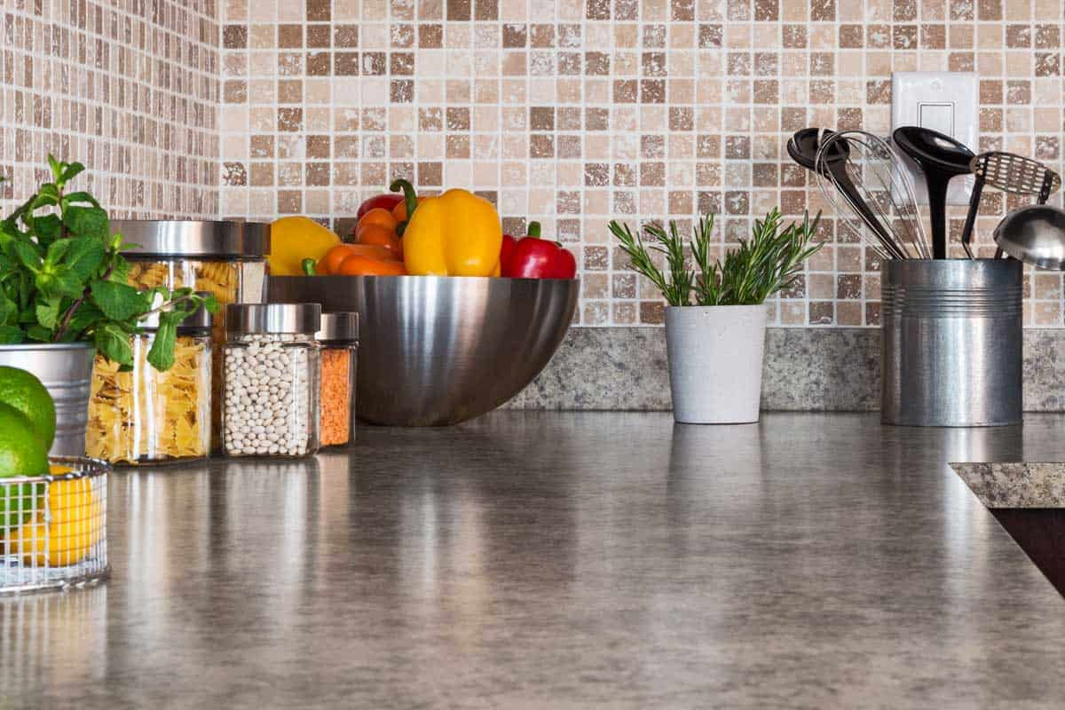 Kitchen countertop with food ingredients and herbs, 11 Stunning Kitchen Backsplash Ideas With Granite Countertops