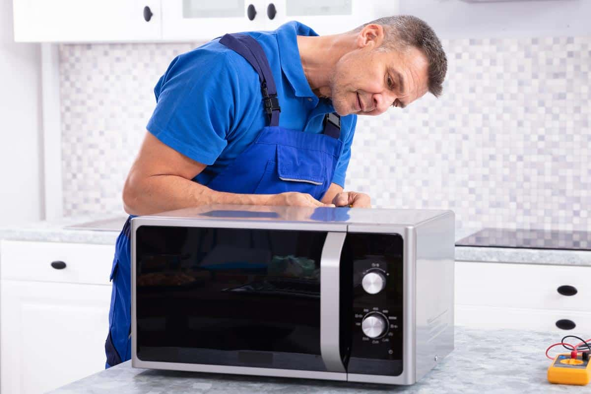 Man repairing microwave oven, Microwave Runs But Not Heating Up - What To Do?