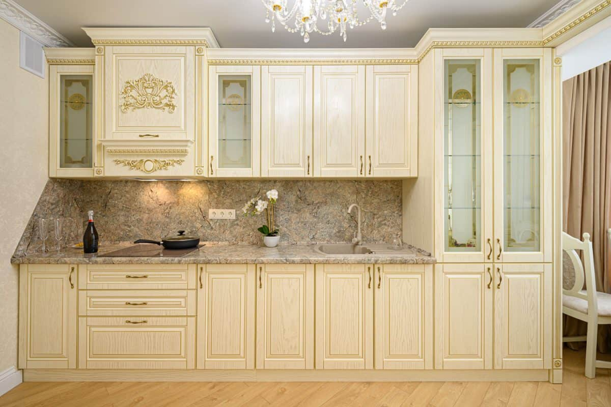 Mid century inspired kitchen cabinets with rustic marble countertops and a chandelier