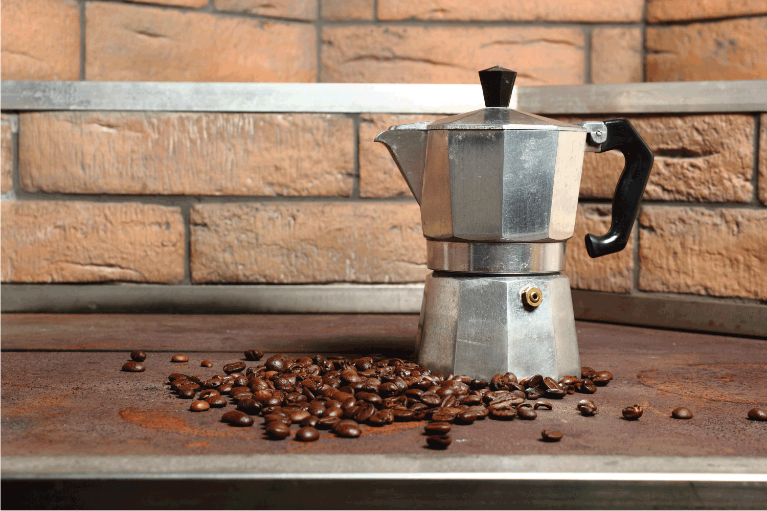 Moka pot and coffee beans on a wooden table, rock wall cladding behind