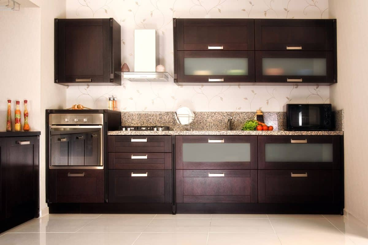 Oak kitchen cabinets with a marble countertop inside a small kitchen with floral wallpaper on the wall