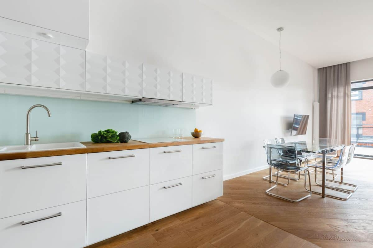 Open space apartment living room with white walls, wooden countertop and white painted kitchen cabinets