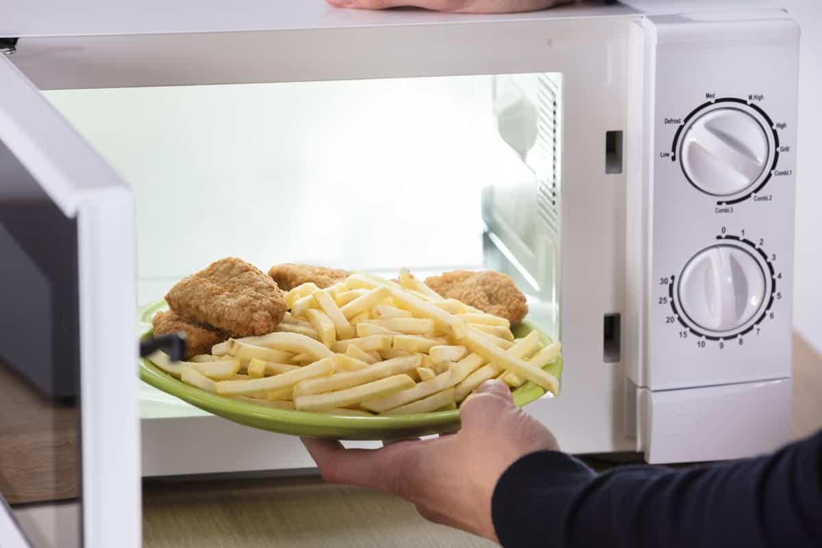 Person putting fried food inside microwave oven, How To Properly Warm Up French Fries [In Multiple Appliances!]