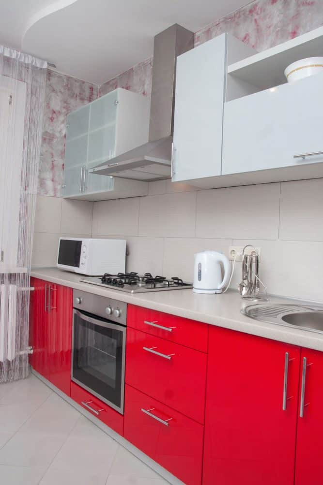 Retro inspired kitchen with red stainless steel drawers, white countertops, white backsplash area nd white kitchen cabinets