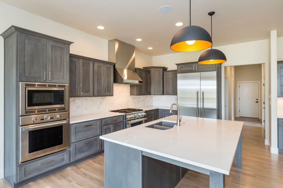 Rustic inspired kitchen with modern approach and recessed lighting with dangling lamps on the breakfast bar