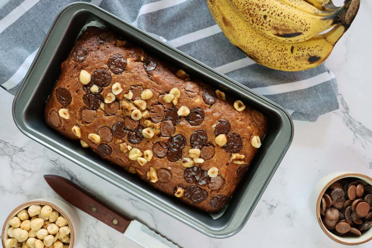 Stock photo showing elevated view of cake loaf tin containing homemade banana loaf, besides a hand of bananas, bowls of chocolate chips and hazel nuts, a tea towel and knife, on a marble effect background., How Full Should A Loaf Pan Be?