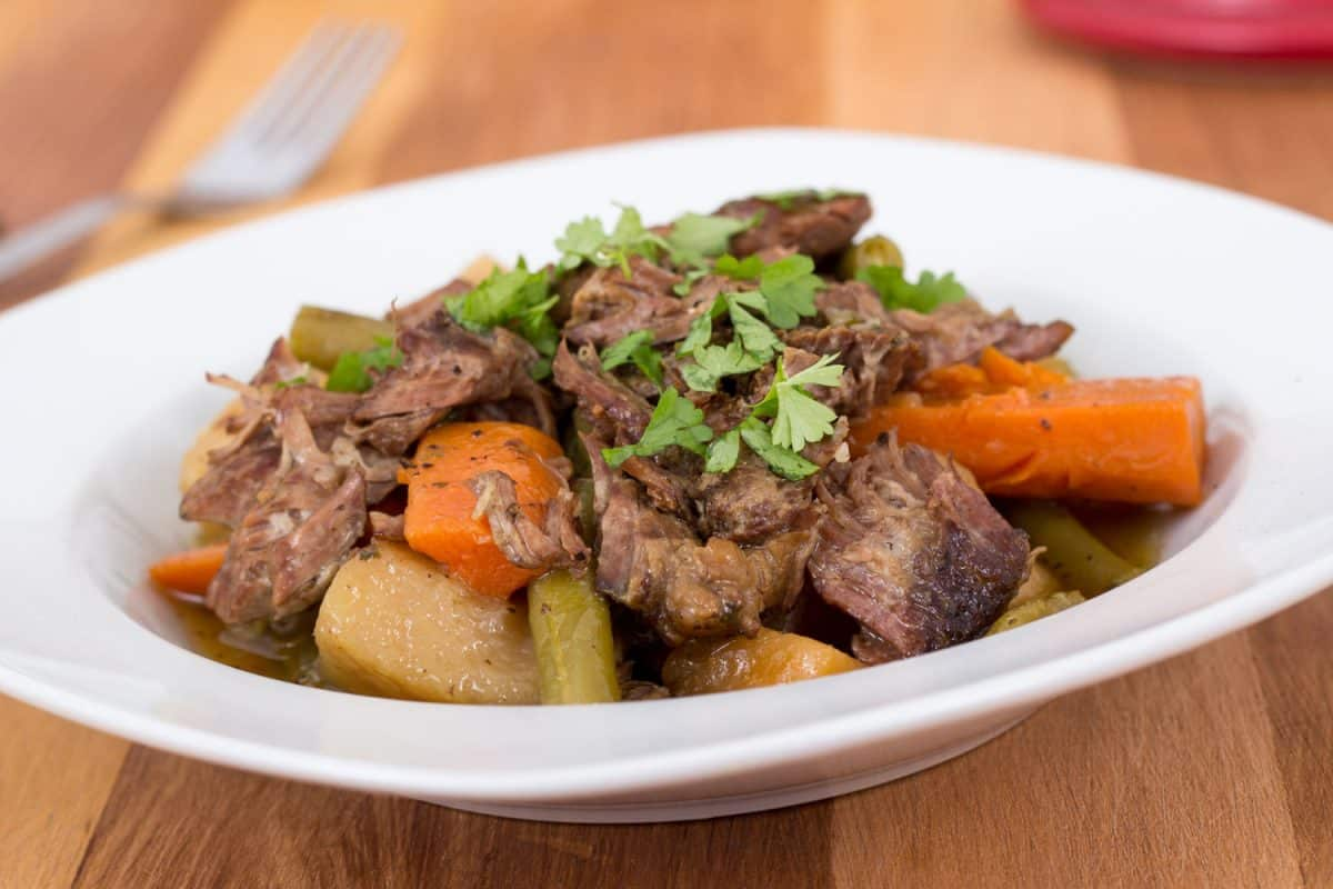 Saucy and mouthwatering pot roast with carrots and potatoes in a small dish