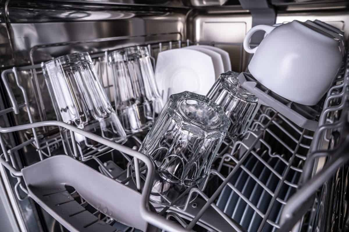 Set of clean dish in dishwasher. Glowing transparent glasses and white cups after washing in dishwasher.