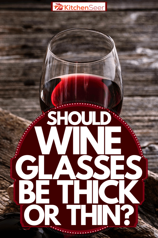 A thick wine glass with red wine placed next to a cork opener, Should Wine Glasses Be Thick Or Thin?