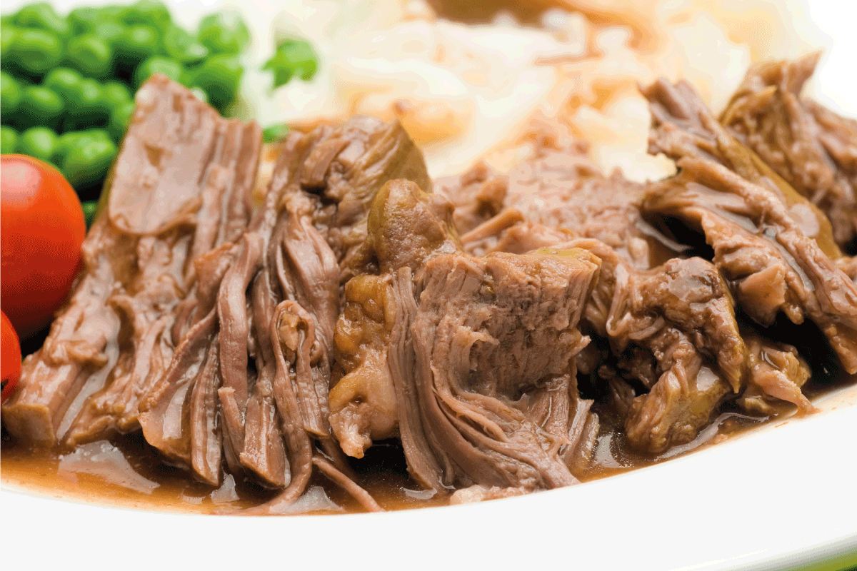 Sliced pot roast dinner on a white plate close up. How Long Should You Cook A Pot Roast