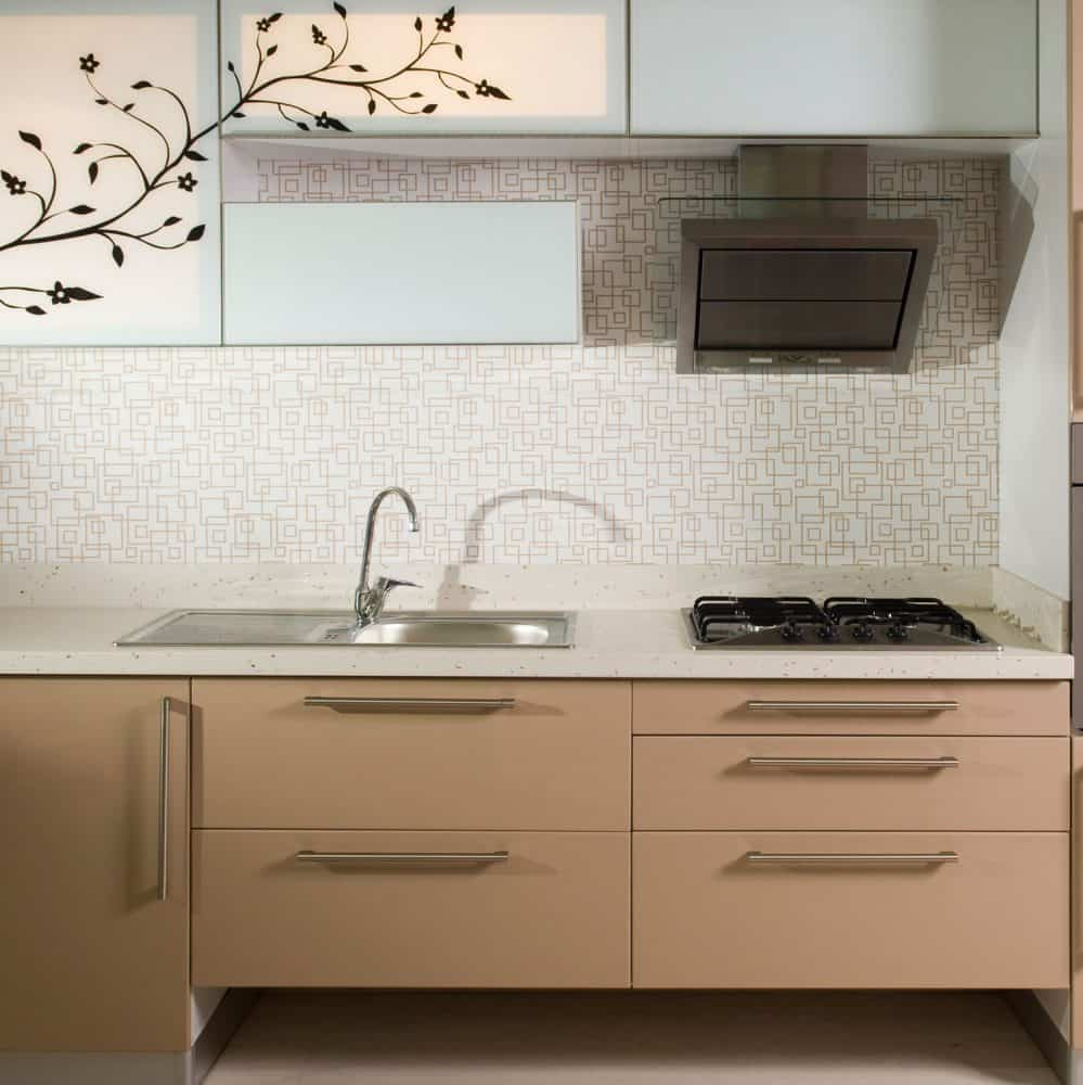 Square patterned kitchen backsplash beige cabinet drawers and a small cooktop and range hood
