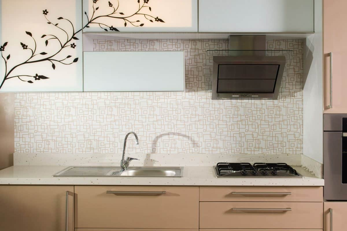 Square patterned kitchen backsplash beige cabinet drawers and a small cooktop and range hood, 21 Best Wallpaper Ideas For Kitchen Walls