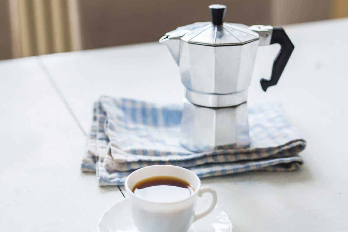 Stainless steel coffee percolator and a cup of coffee on the table, How To Clean A Stainless Steel Coffee Percolator