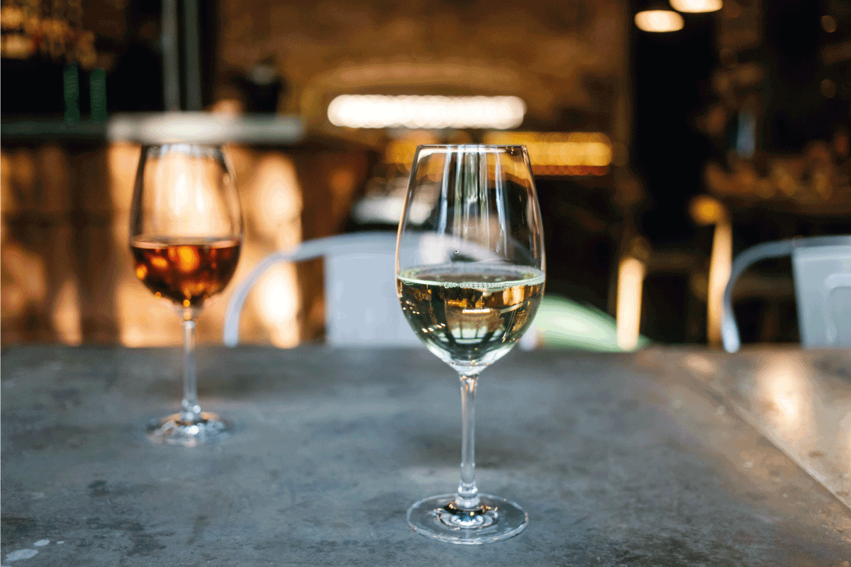 Two glasses of wine white and rose standing on a table in a restaurant setting. How Should You Hold A Red Wine Glass
