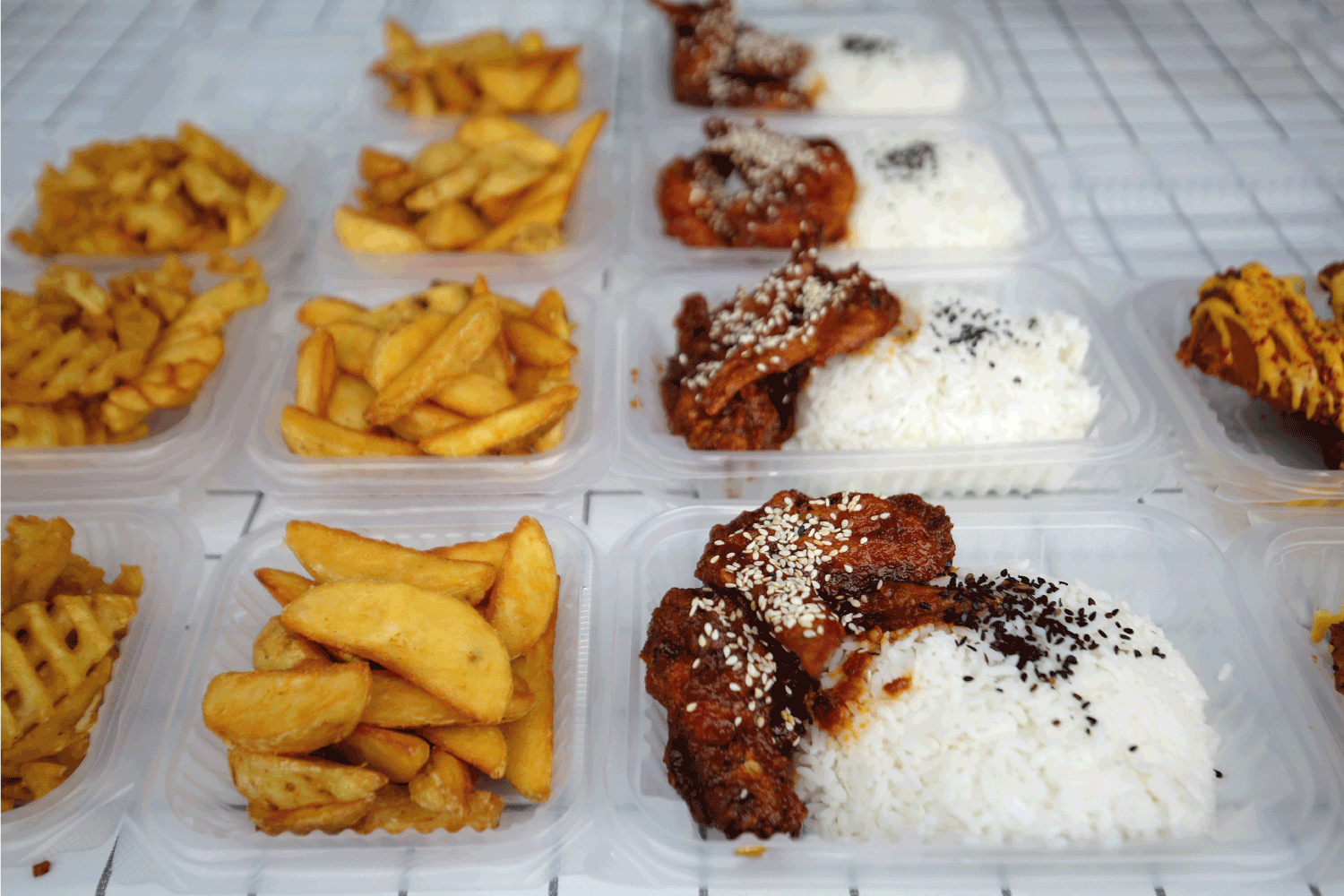 Varieties of lunch box food and potato wedges in pre-packaging for hygiene and shoppers' convenience.