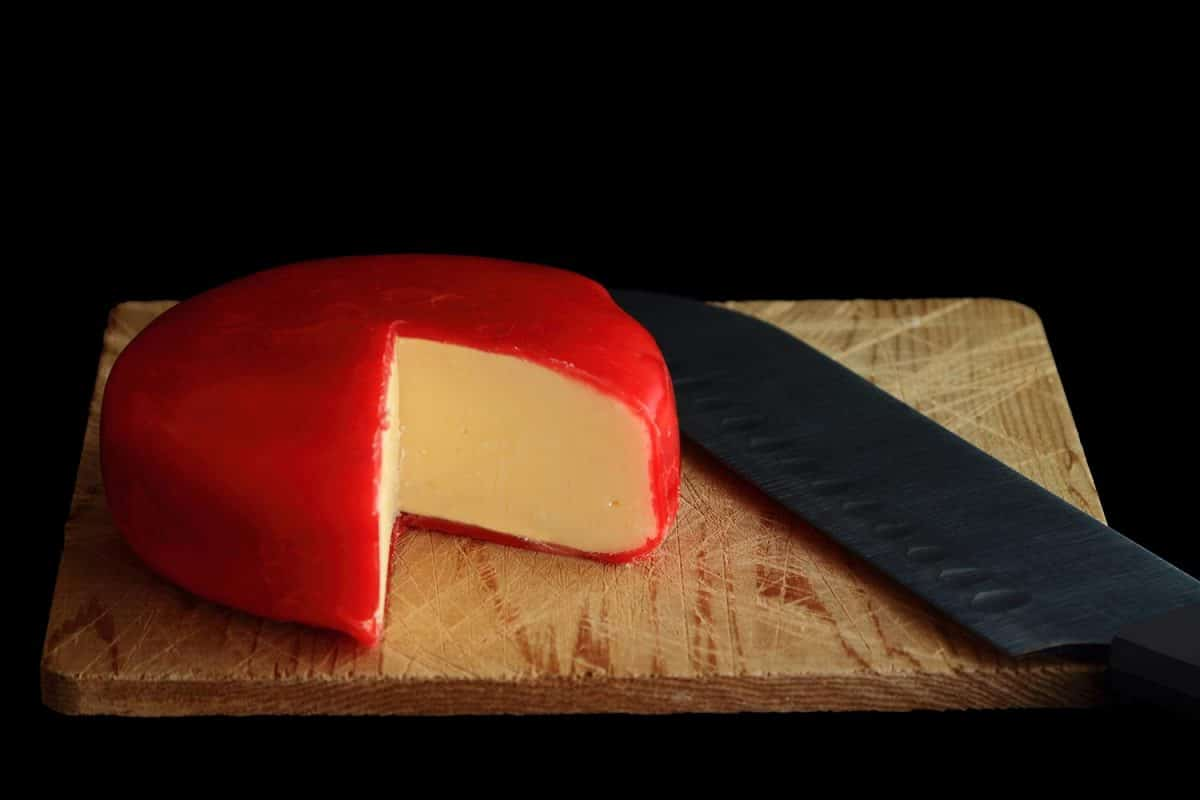 Wheel of Gouda Cheese covered with red wax protective layer over wooden cutting board