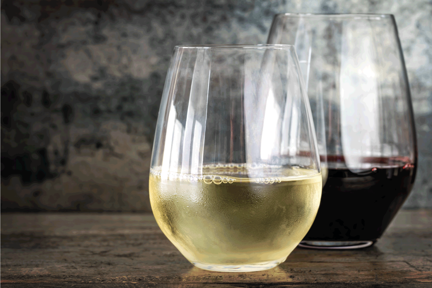 White and red wine in modern stemless glasses, with slate and timber background