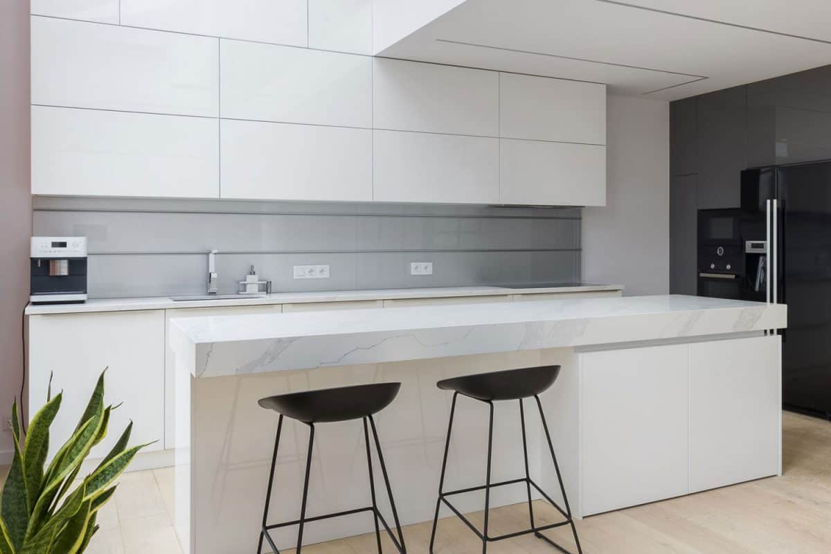 White inspired kitchen with white countertop, black bar stools and white kitchen cabinetry