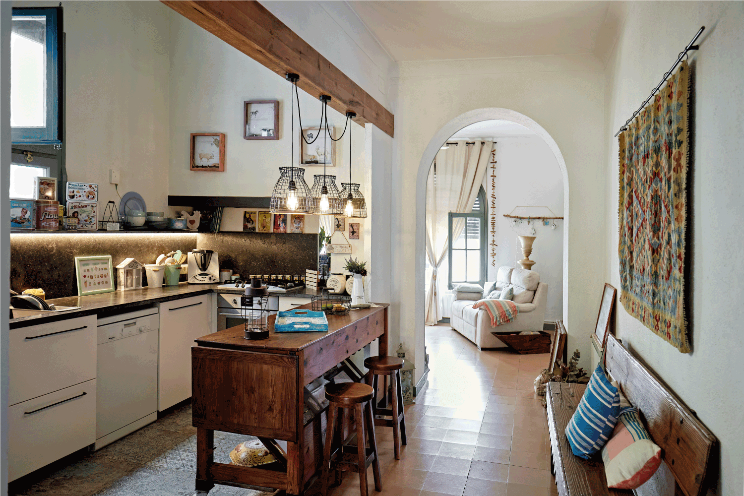 Wide angle view of kitchen with wooden counter-height dining table and stools, hanging light fixtures, bench
