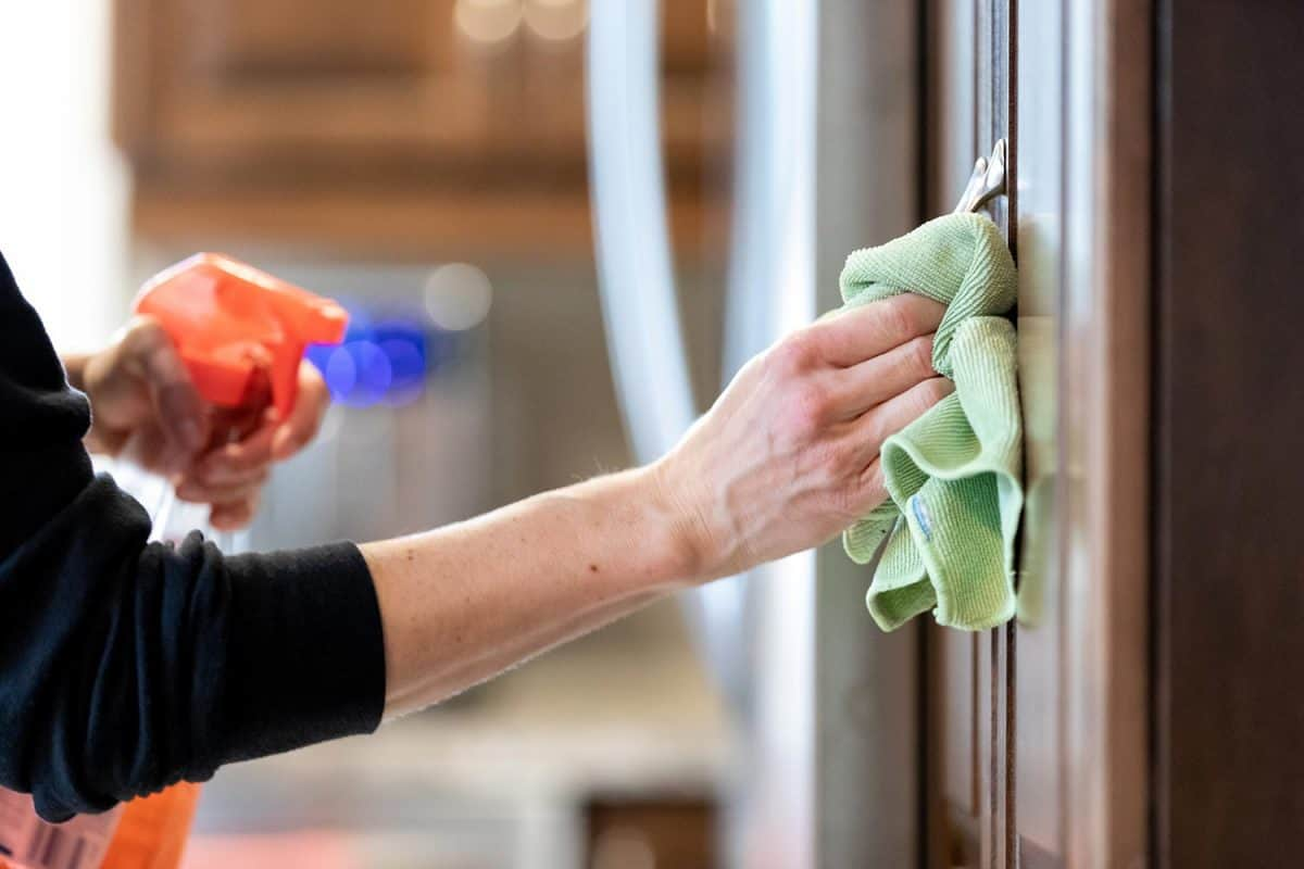 Woman cleaning kitchen cabinet handle with disinfectant product