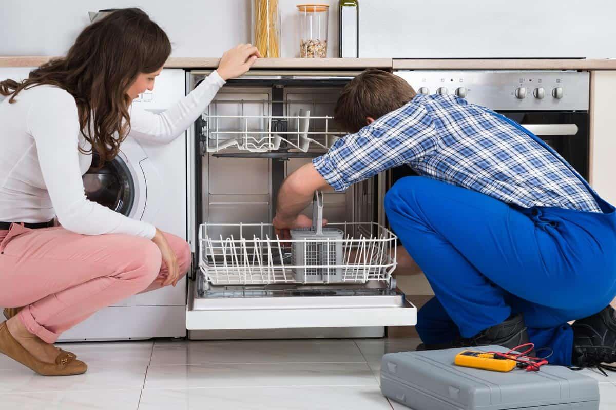 Woman looking at repairman repairing the dishwasher