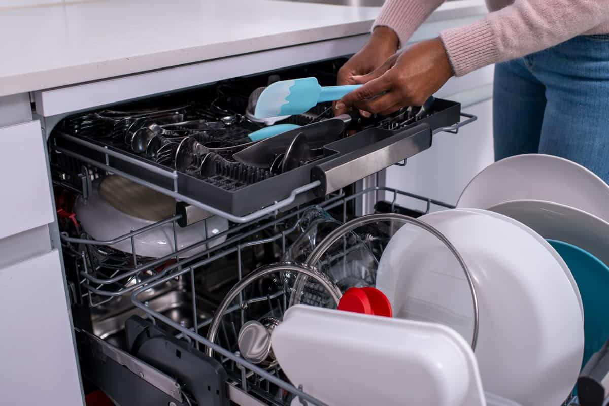 Woman unloading dishwasher after washing, How To Secure A Dishwasher To The Cabinet