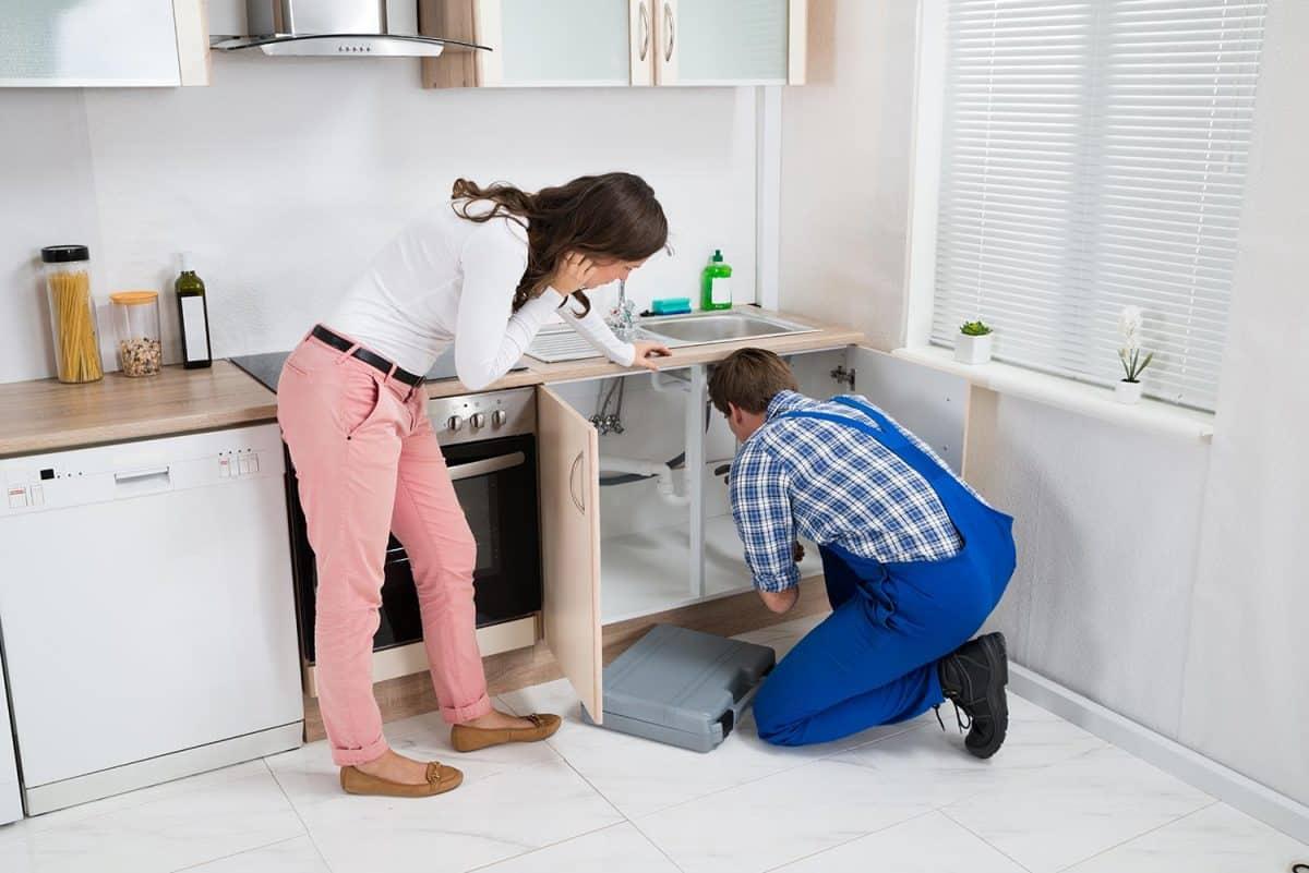 Woman watching as worker repairing sink pipe