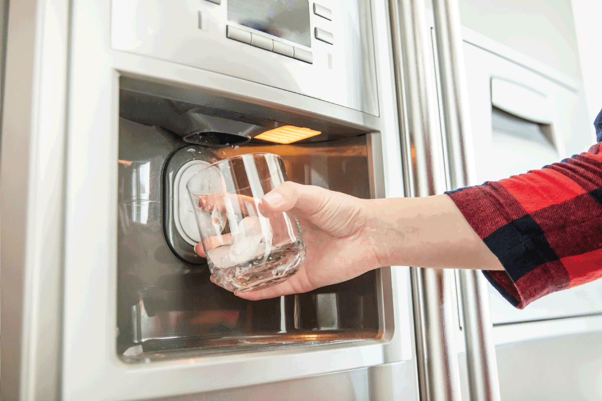 Woman's hand holds glass and uses refrigerator to make fresh clean ice cubes. How Long To Defrost Samsung Ice Maker