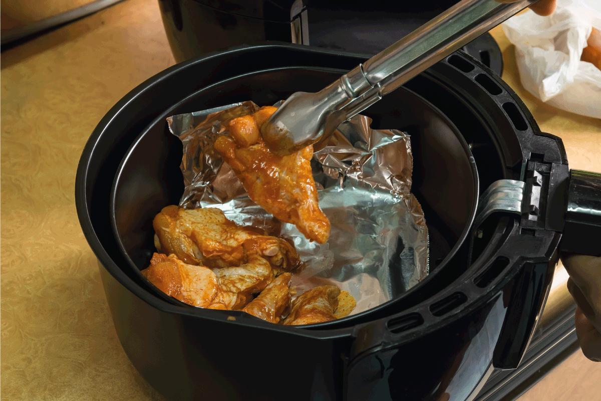 chicken legs being arranged inside an air fryer with aluminum foil