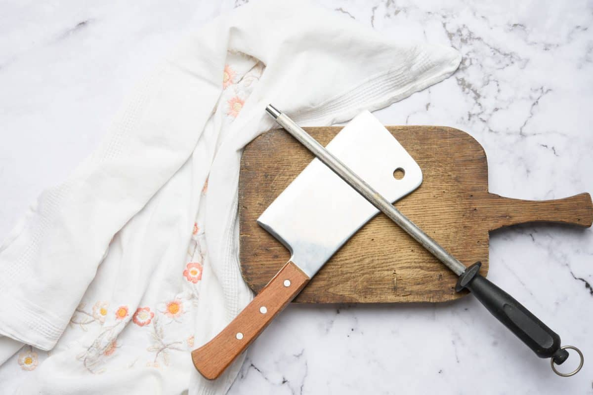 knife and old iron sharpener with handle for kitchen knives on a white background, Do Knife Sharpeners Wear Out? [And When To Replace Yours]