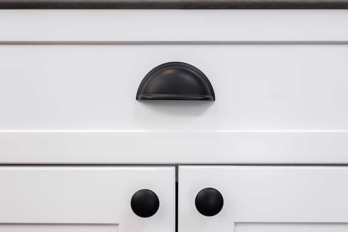 A white kitchen drawer with a cup handle and black colored knobs