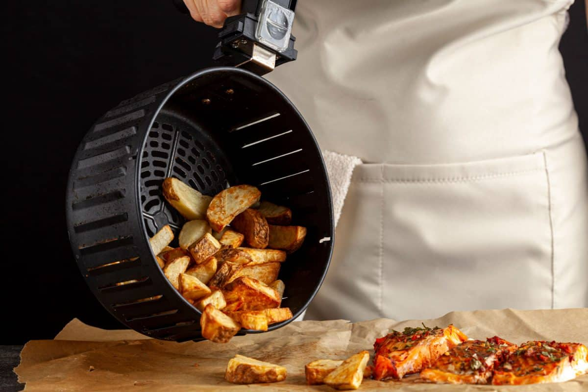 A woman pouring fried potatoes from the air fryer