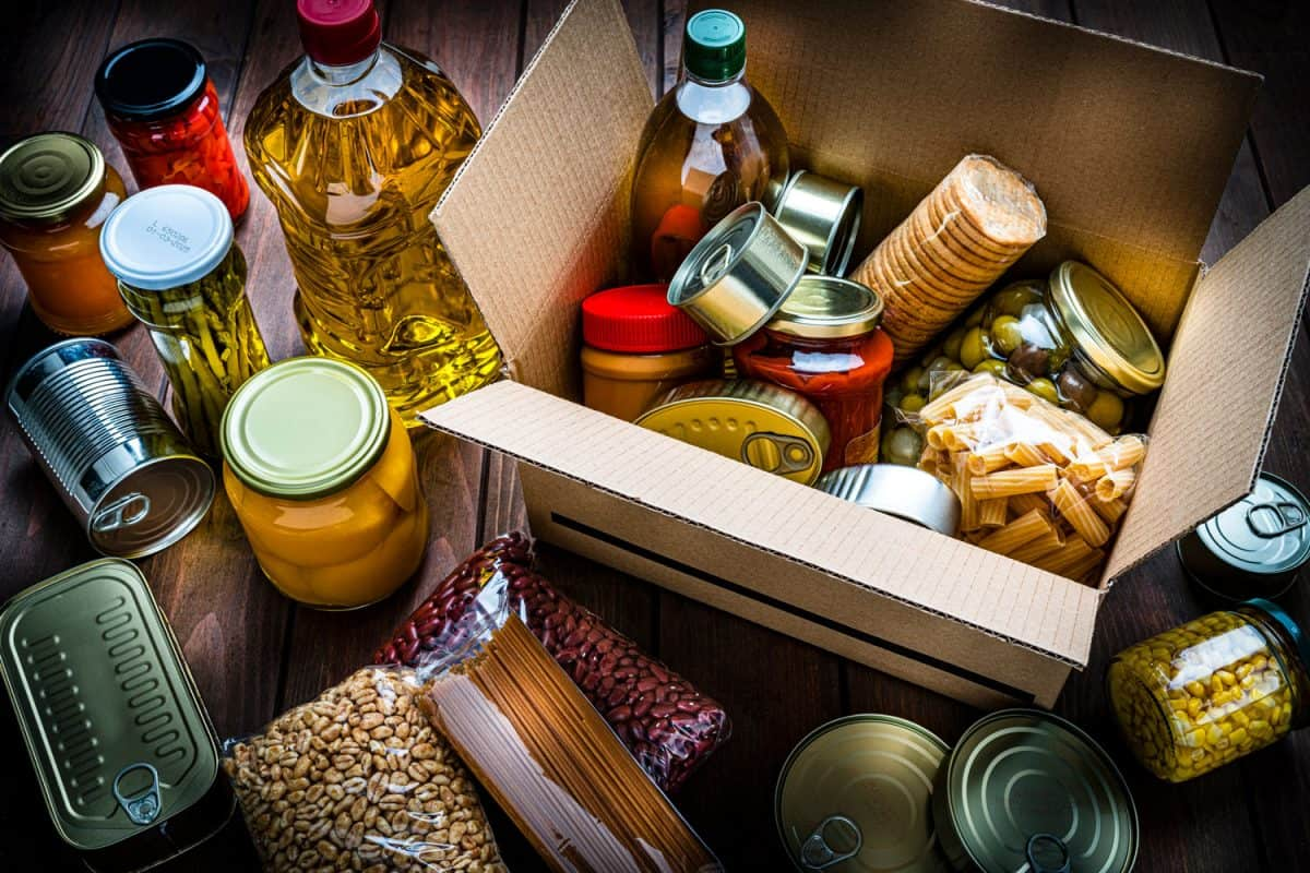 Canned goods with other cooking oils and nuts in containers inside a cardboard box