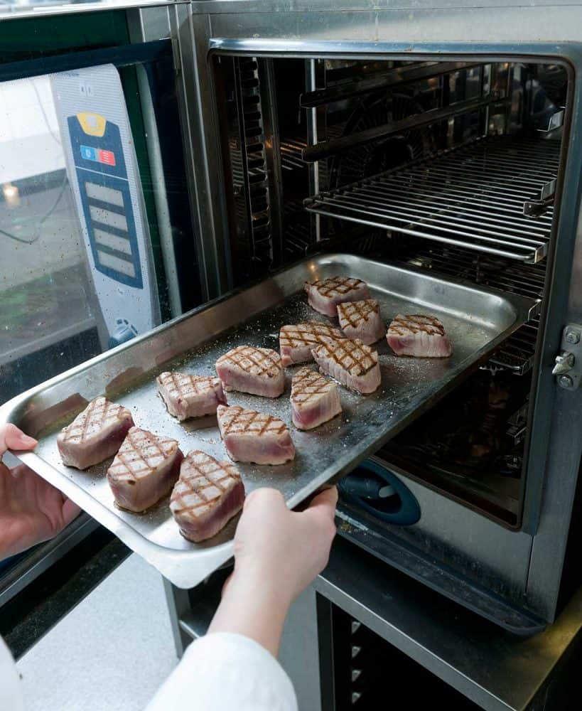 Close up on chef putting plate with char-grilled tuna steaks into the oven