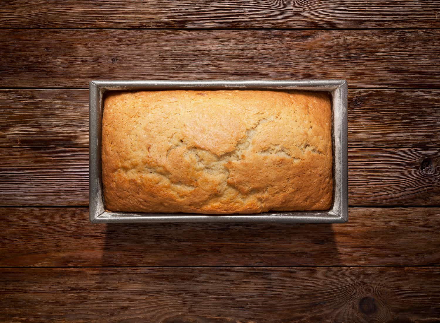 Fresh Cake on loaf pan on Wooden Background