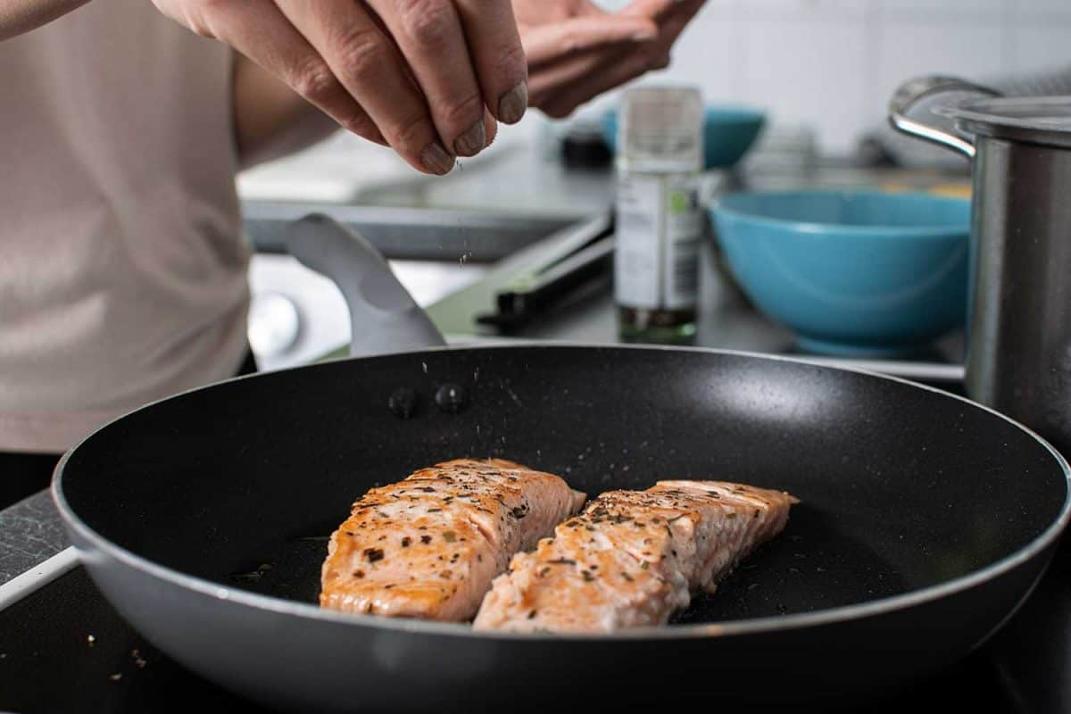 Fried salmon cooking on the hob and adding herbs and spices