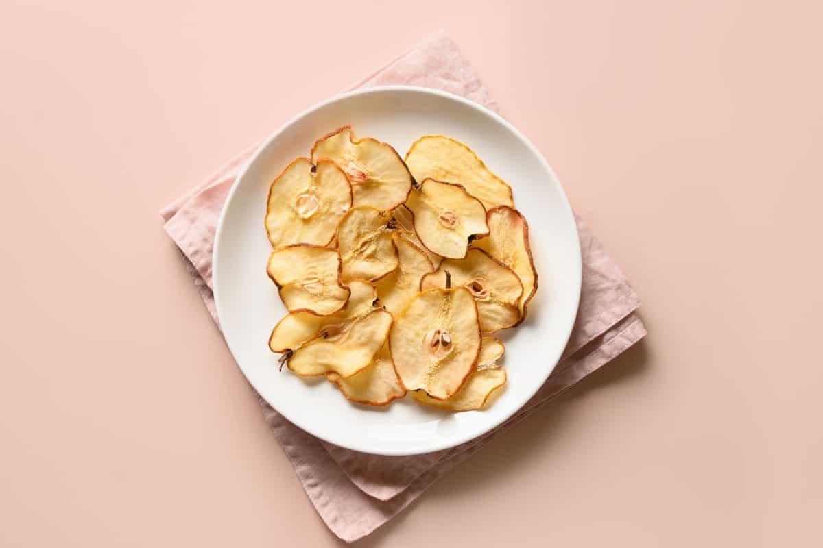 Fruits pear chips on a beige background. Vegan dessert sugar free