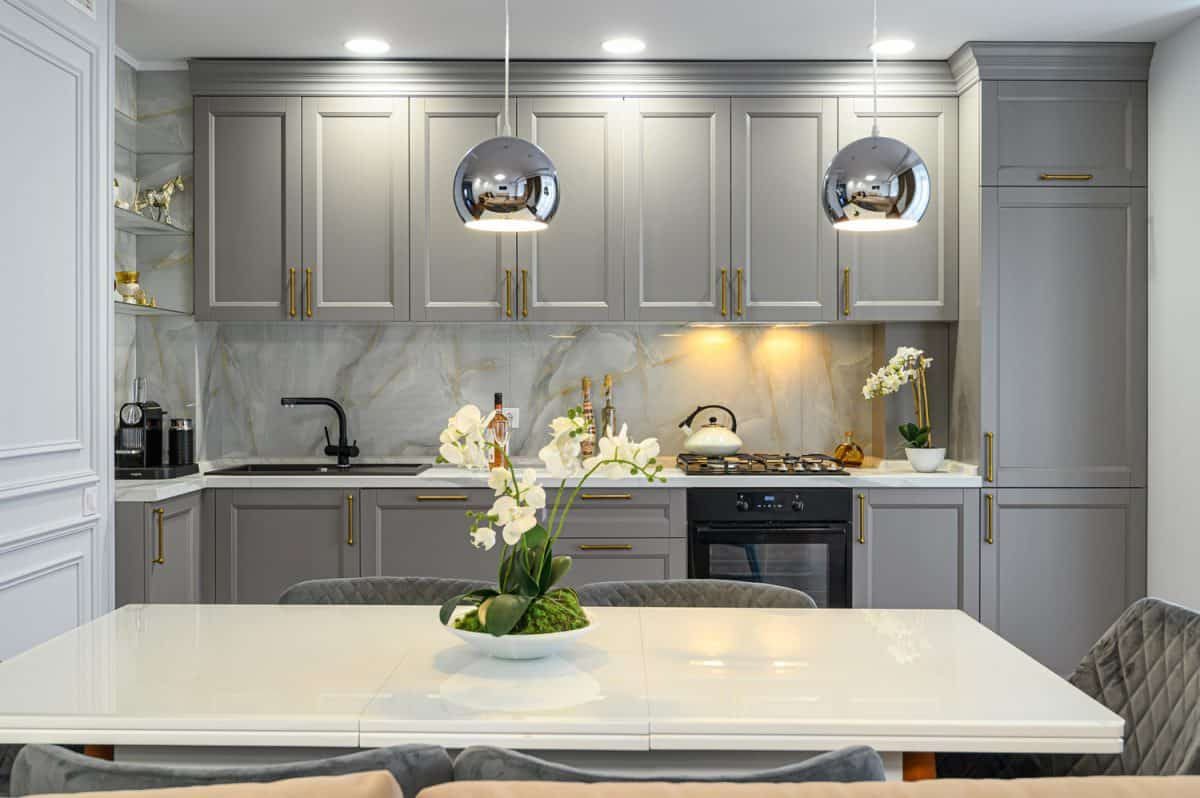 Grey and white contemporary classic kitchen interior with dining table designed in modern style, front view