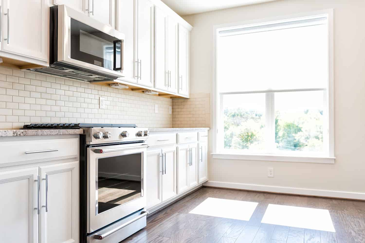 Modern gray, brown neutral kitchen features front cabinets with granite countertops and tile backsplash, window in contemporary home, Should Kitchen Cabinets Match Your Trim?
