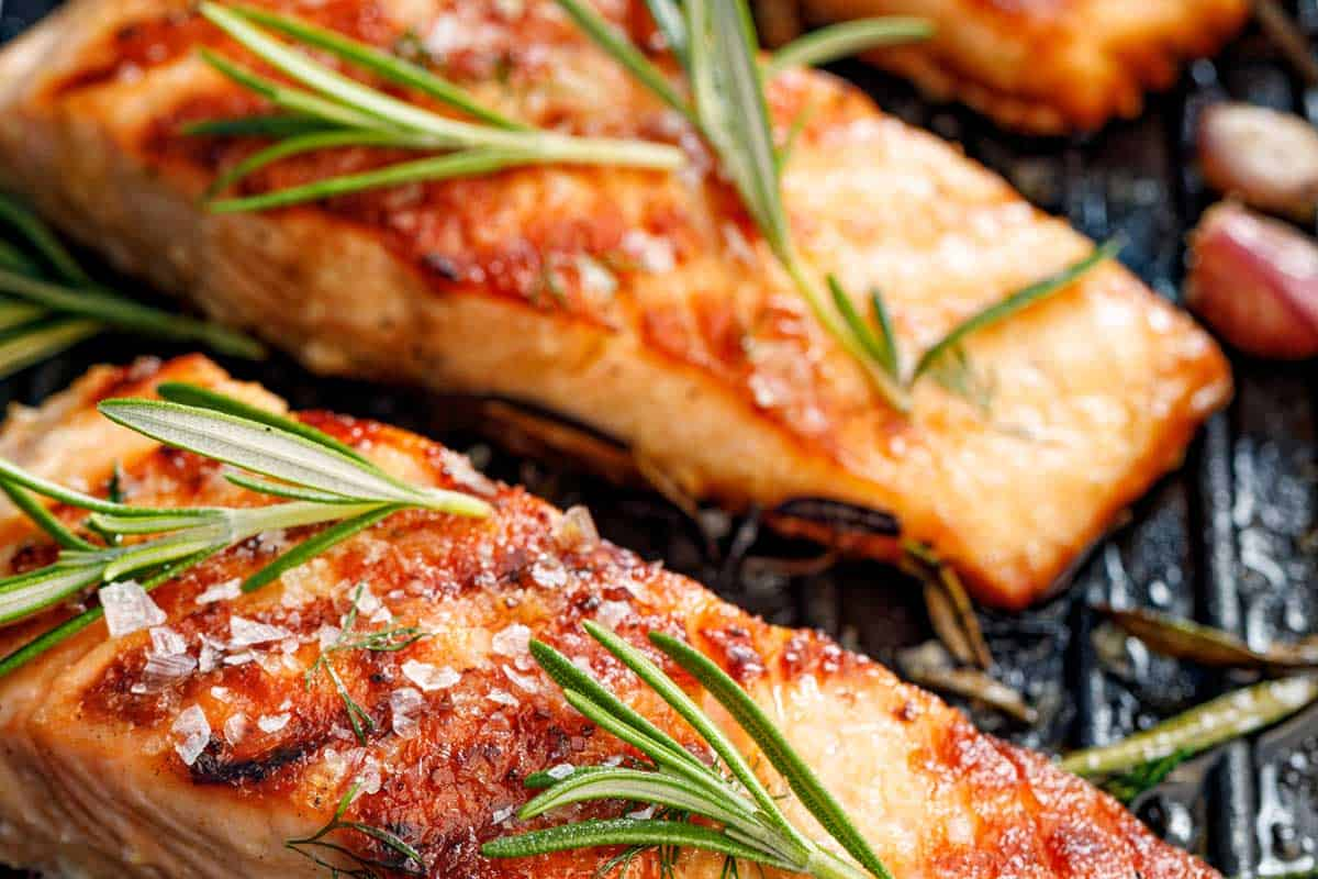 Salmon fillets sprinkled with fresh herbs and lemon juice on a grill plate, Should You Fry Or Bake Salmon?