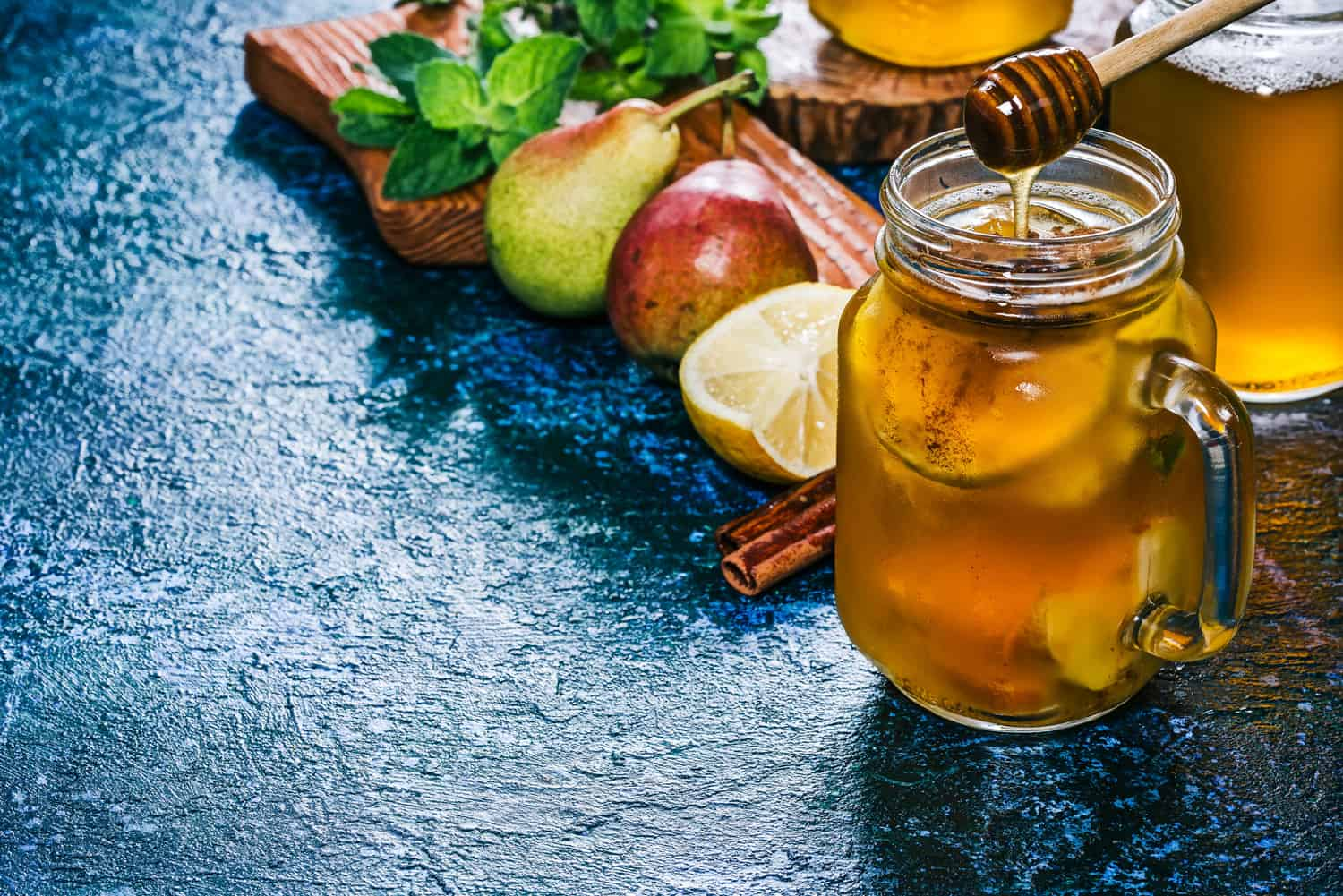 Sangria with pear cider, fresh pears and lemon, honey and cinnamon in mason jar with ingredients. Spotty blue background.