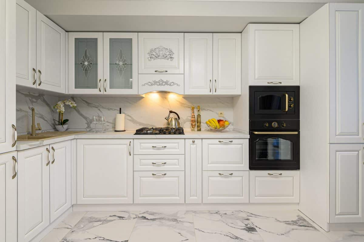White cozy modern classic kitchen interior with wooden furniture and appliances, front view